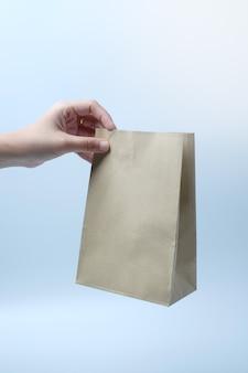 Mão segurando um saco de papel