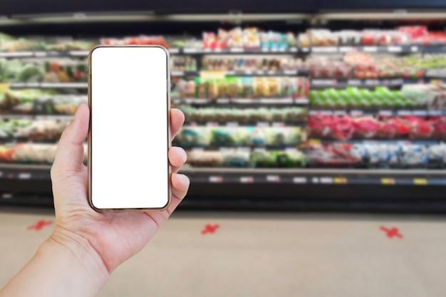 Mão segurando um smartphone em branco no supermercado