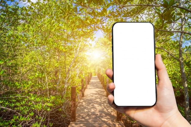 Mão segurando um smartphone em branco sobre fundo de paisagem natural