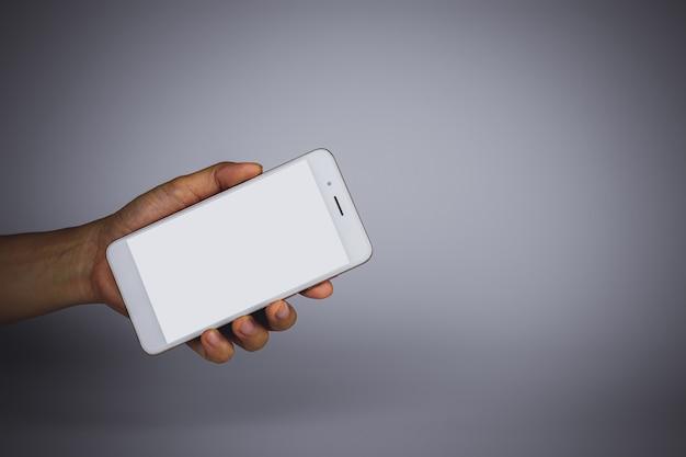 Mão segurando um smartphone móvel com tela branca em branco.