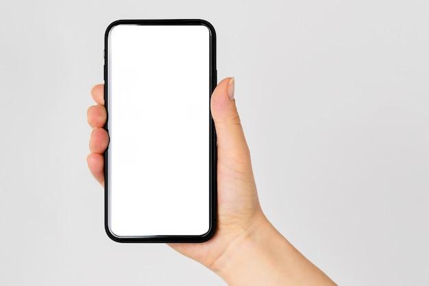 Mão segurando um smartphone preto isolado no traçado de recorte de fundo branco