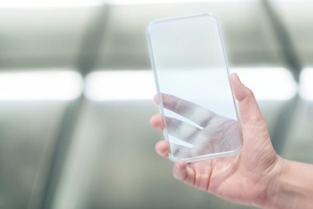Mão segurando um smartphone transparente com fundo de efeito de luz neon