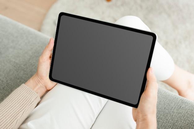 Mão segurando um tablet digital com uma tela preta em branco