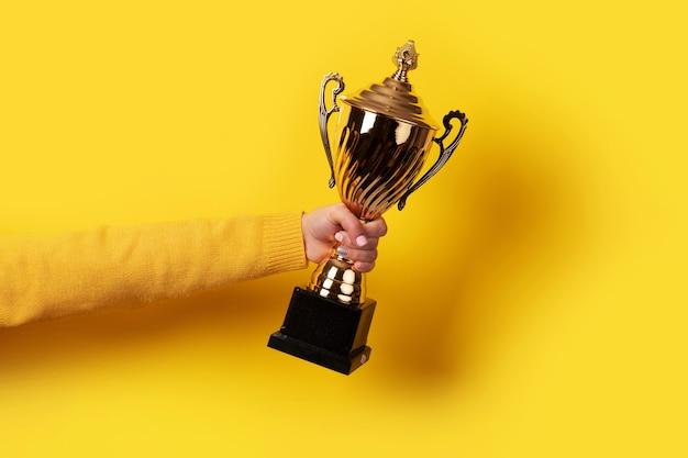 Mão segurando um troféu dourado sobre fundo amarelo