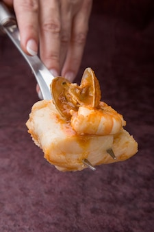 Mão segurando um utensílio de cozinha com uma porção de amêijoas com pescada em fundo escuro
