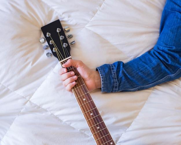 Mão segurando um violão na cama, criatividade do artista, implacavelmente.