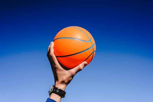 Mão segurando uma bola de basquete laranja no fundo do céu azul, convite para jogar