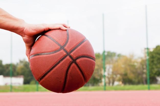 Mão segurando uma bola de basquete