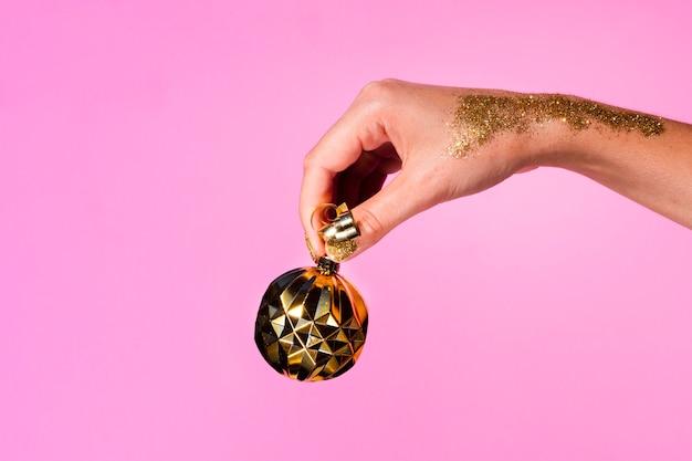 Mão segurando uma bola de decoração dourada