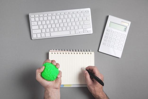 Mão segurando uma bola de estresse verde na mesa de negócios.