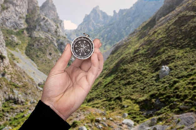 Mão segurando uma bússola atrás de uma paisagem montanhosa