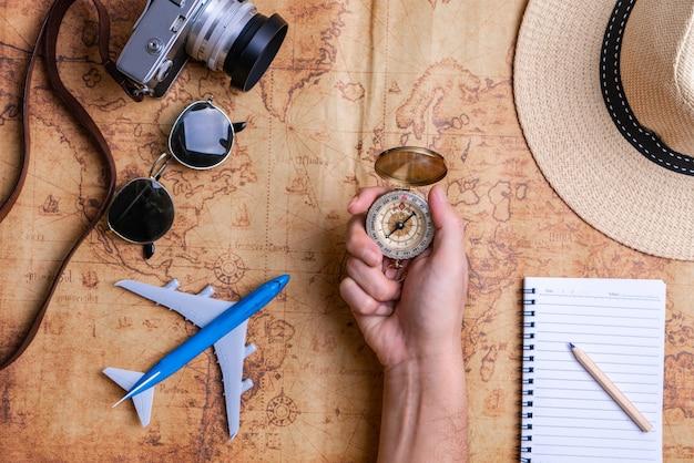 Mão segurando uma bússola com acessórios para o conceito de viagens