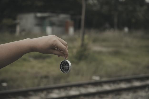 Mão segurando uma bússola para encontrar destinos de viagem. estilo vintage.