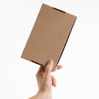 Mão segurando uma caixa de papelão