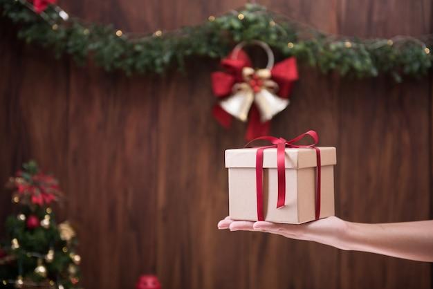 Mão segurando uma caixa de presente com decoração de feliz natal e feliz ano novo
