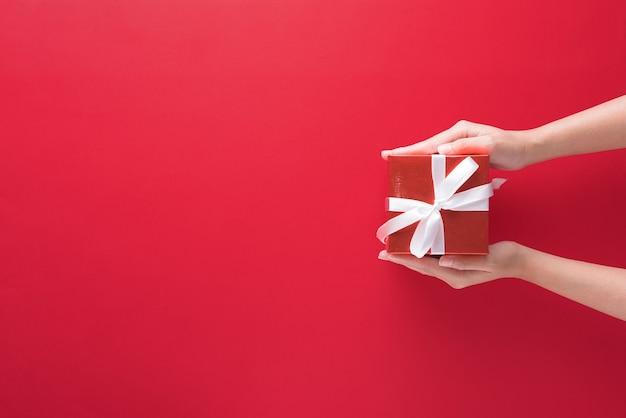 Mão segurando uma caixa de presente com feliz natal e feliz ano novo