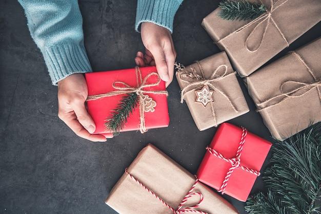 Mão segurando uma caixa de presente de natal com decoração