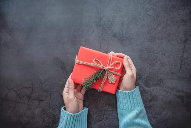 Mão segurando uma caixa de presente de natal