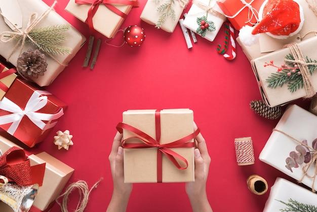 Mão segurando uma caixa de presente por ocasião da decoração de feliz natal e feliz ano novo