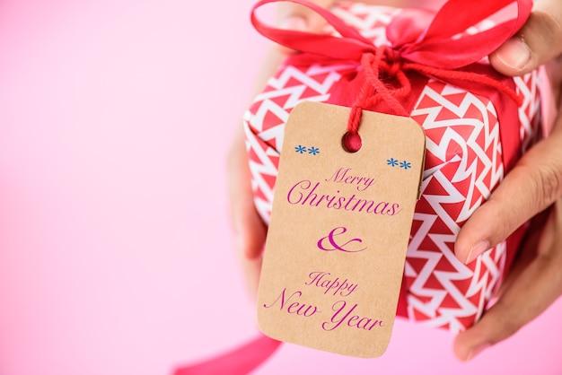 Mão segurando uma caixa de presente vermelha com tag de saudação