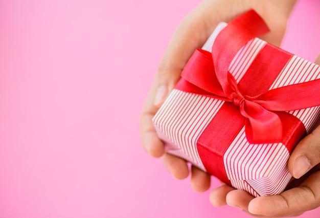 Mão segurando uma caixa de presente vermelha em fundo rosa