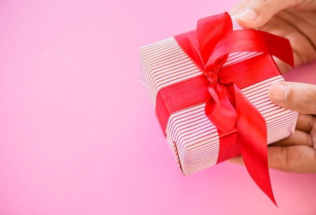 Mão segurando uma caixa de presente vermelha em fundo rosa.
