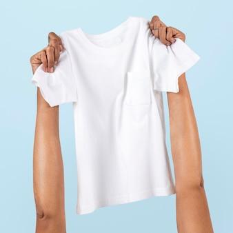 Mão segurando uma camiseta infantil