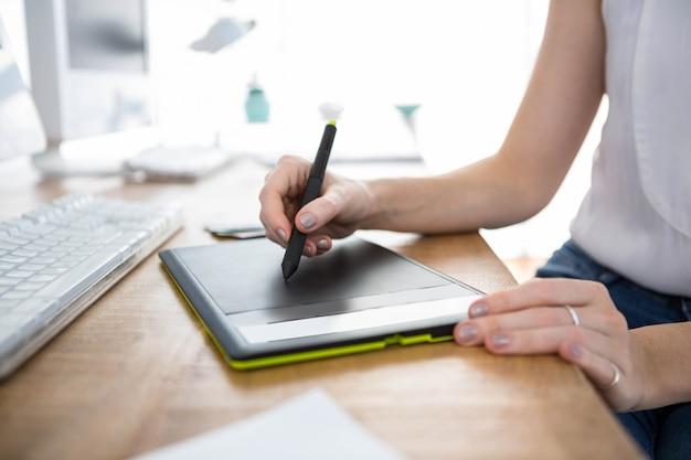 Mão segurando uma caneta que está desenhando em um tablet de desenho digital