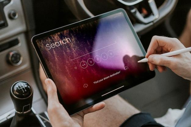 Mão segurando uma caneta stylus pesquisando em um tablet em um carro