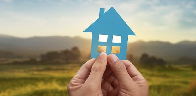 Mão segurando uma casa de papel azul com fundo de paisagem