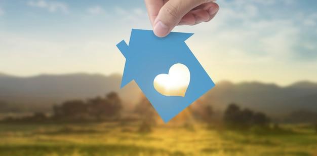 Mão segurando uma casa de papel azul com uma janela em forma de coração no fundo da paisagem