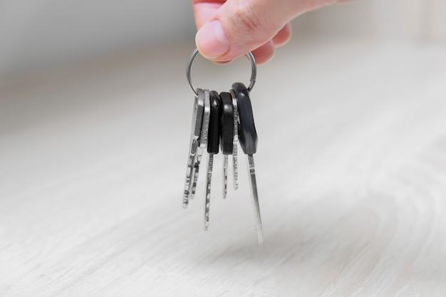 Mão segurando uma chave em casa, saindo de casa e pegando as chaves da mesa ou prateleira