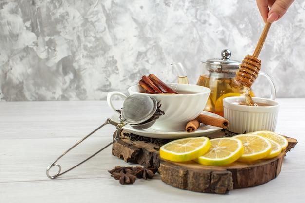 Mão segurando uma colher com chá preto mel em uma xícara branca na mesa branca