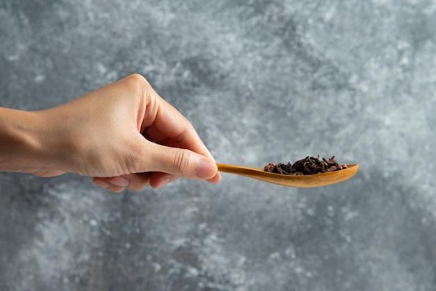 Mão segurando uma colher de pau com cravo seco.