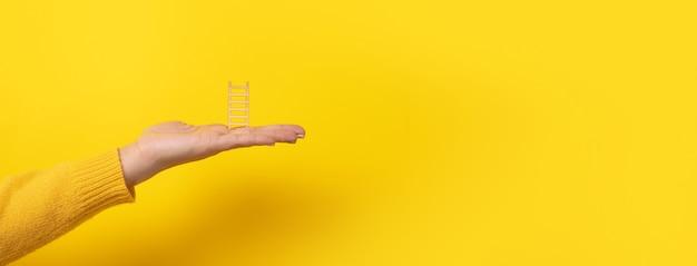 Mão segurando uma escada sobre fundo amarelo, conceito de educação e sucesso