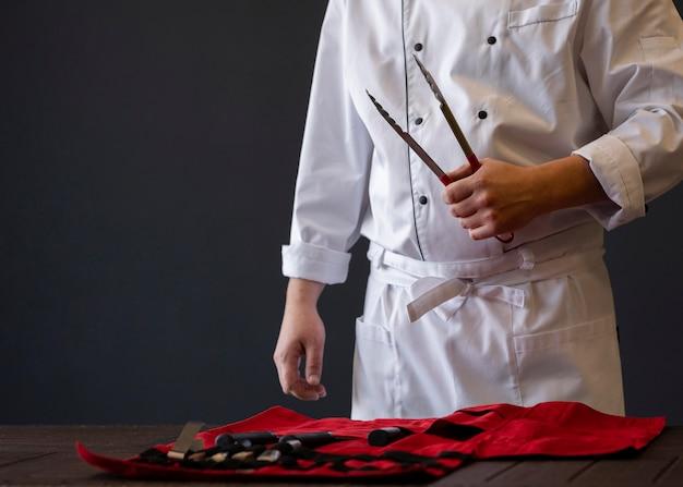 Mão segurando uma ferramenta de churrasco