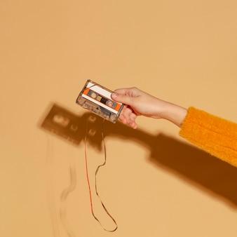 Mão segurando uma fita cassete velha