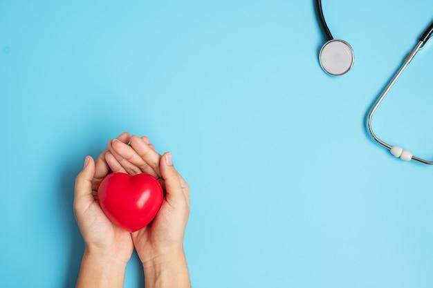 Mão segurando uma forma de coração vermelho com estetoscópio