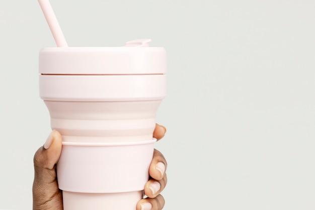 Mão segurando uma foto em forma de copo dobrável rosa com espaço de design