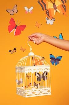 Mão segurando uma gaiola de pássaro com iconos borboletas