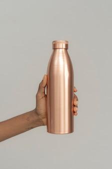 Mão segurando uma garrafa de cobre de aço inoxidável