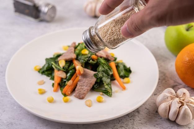 Mão segurando uma garrafa de gergelim branco servindo comida.