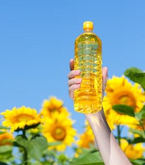 Mão segurando uma garrafa de óleo de girassol