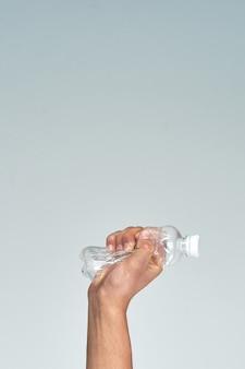 Mão segurando uma garrafa de plástico