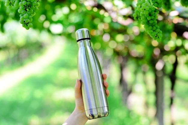 Mão segurando uma garrafa termo-brilhante de aço reutilizável para água no fundo do vinhedo