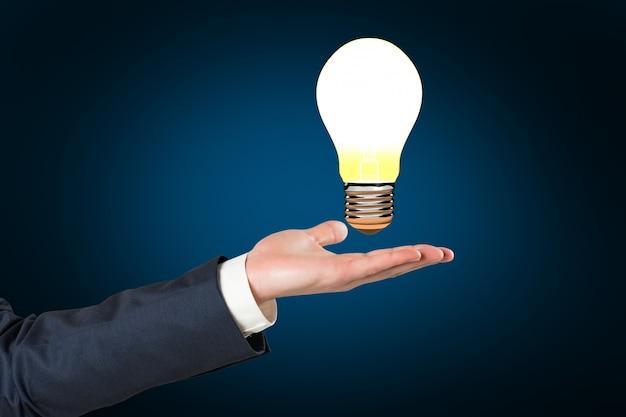 Mão segurando uma lâmpada acesa