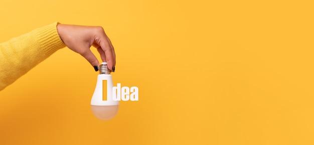Mão segurando uma lâmpada com a ideia de inscrição, maquete panorâmica