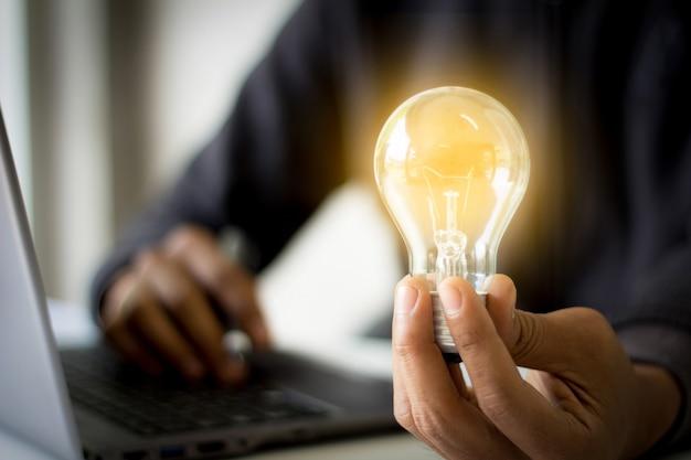 Mão segurando uma lâmpada com um laptop ao fundo