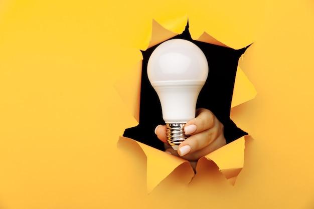 Mão segurando uma lâmpada de led incandescente de um buraco rasgado em papel amarelo.