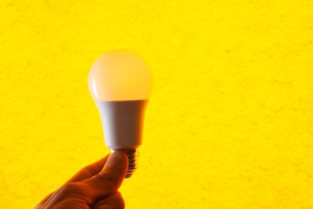 Mão segurando uma lâmpada em um fundo amarelo
